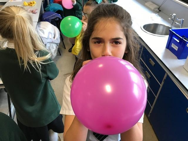 Blowing up balloons to help us create static energy.