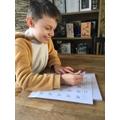 Enjoying his maths work.