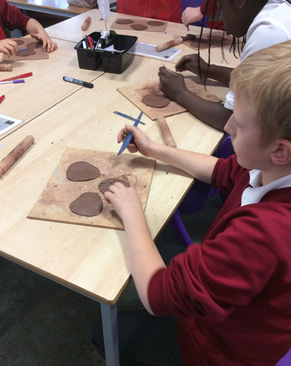 Working hard to carve the clay for our fossils!