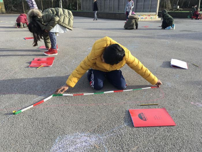 Measuring shadows using tape measures.