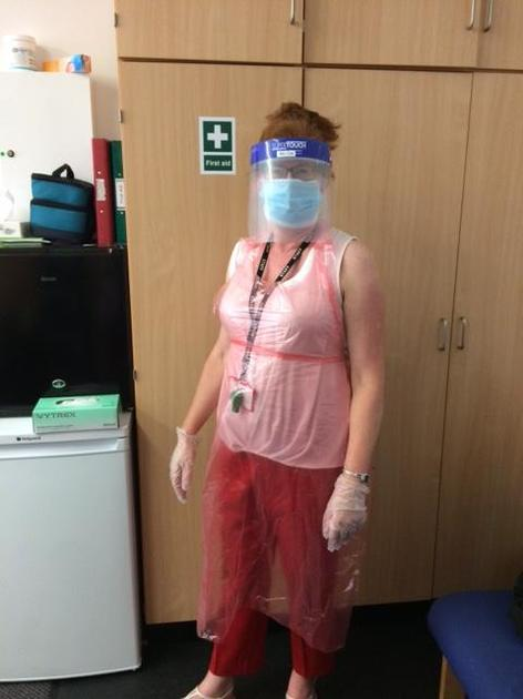 Mrs Coe wearing a mask, apron and shield