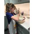 Hannah bakes a cake by hand.