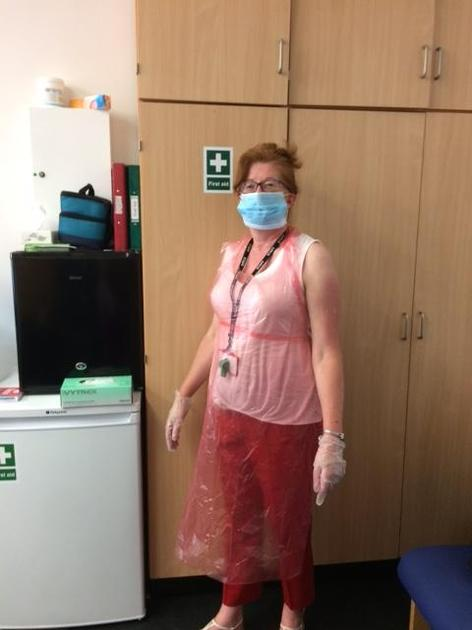 Mrs Coe with wearing a mask and apron