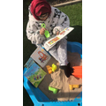 Mrs Iqbal reading in the sand pit.j