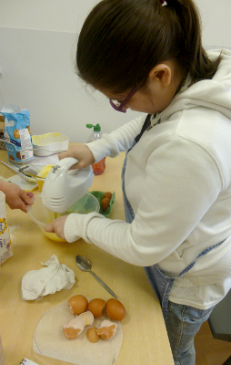 Pupil mixing eggs with an electric hand whisk
