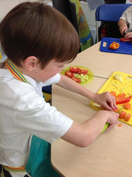 Using the claw grip carefully to cut peppers.