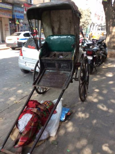Having a rest in the Sun under his rickshaw