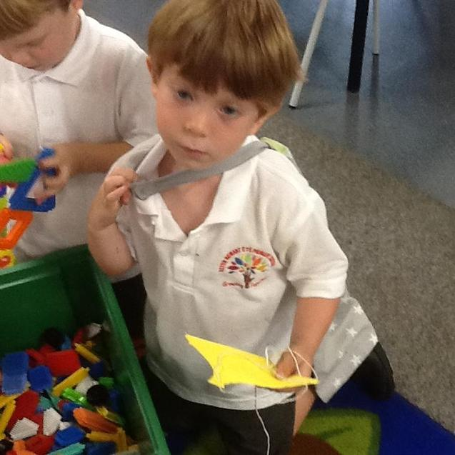 This clever clogs made a cape by using a pencil to make holes and threading string through