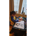 Lucy is drawing a picture of a cat which is her favourite animal!
