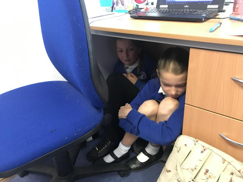 The girls were protecting their books by hiding form the soldiers...
