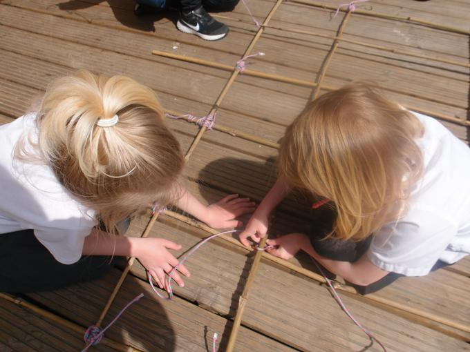 Working together to hold the bamboo still and square lash the sticks together