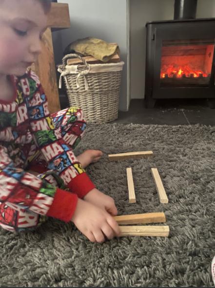 Oscar using sticks to find different ways to make 5