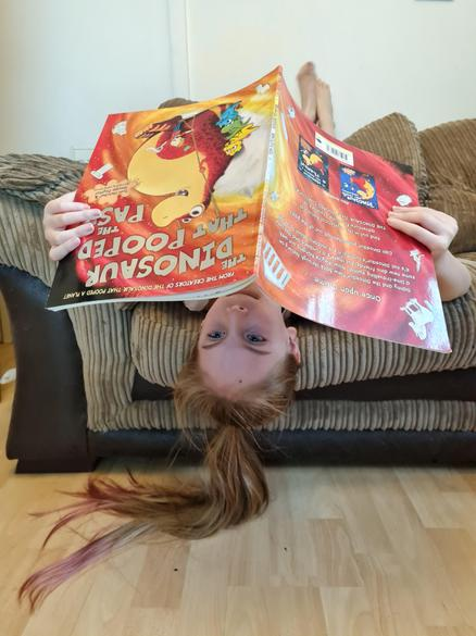 Pandora from Year 3 reading her book upside down