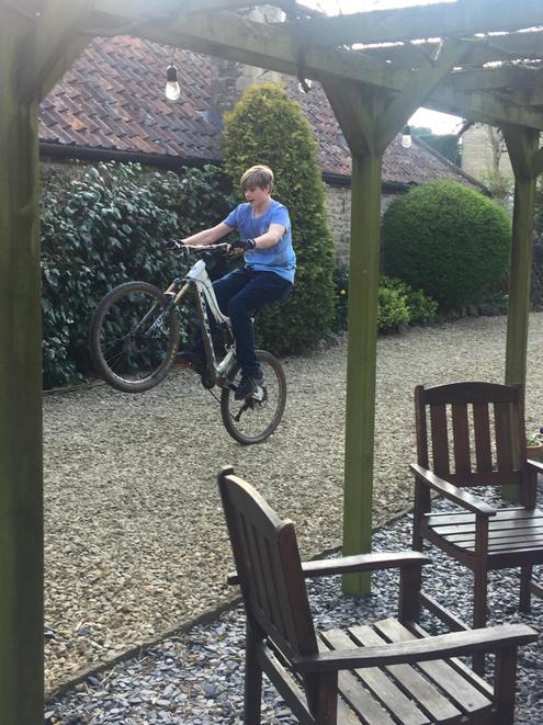 Ben practising his wheelies in the garden.