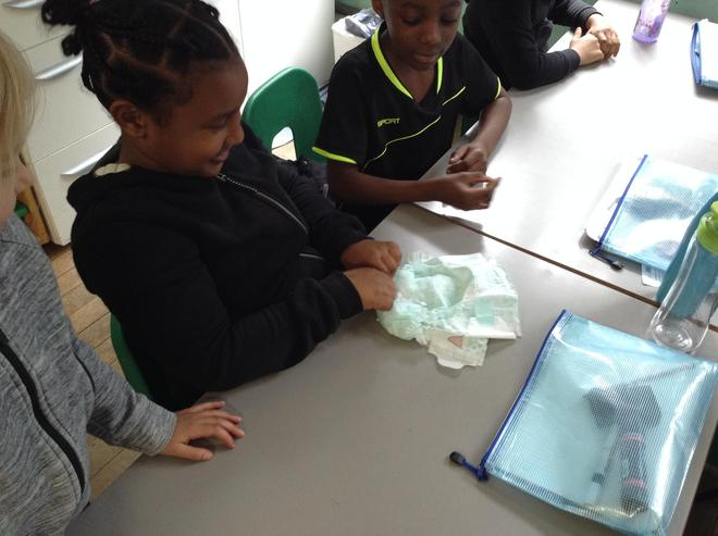 Here the children are making a nappy after we spoke about which materials would be best.