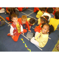 Children participating in a Maths activity, in which they are to count the number of objects in their bowls.