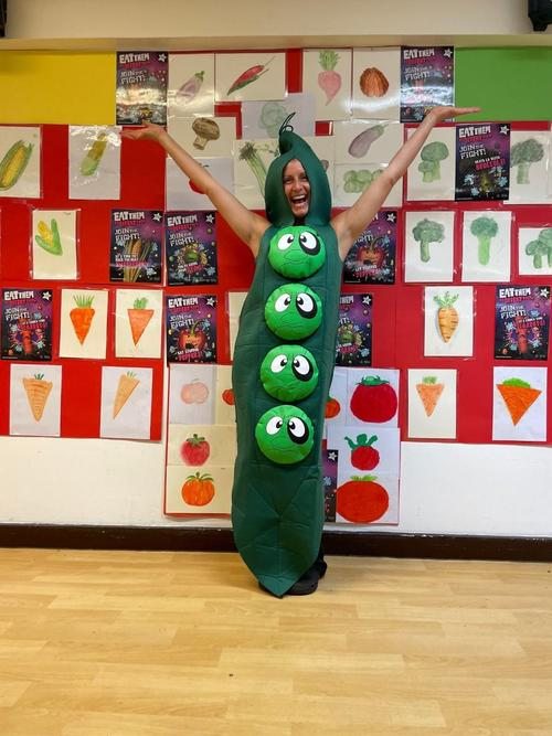 Our Catering Manager Natalie in costume with pictures from our children of some of the vegetables they have been tasting
