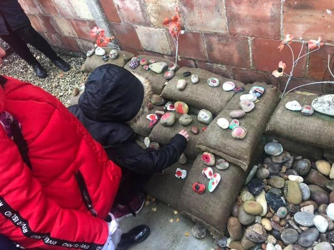 Children laying pebbles to show Remembrance