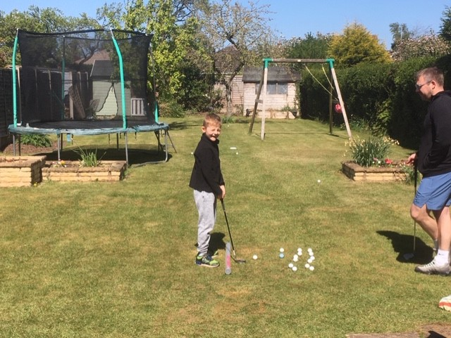 Sam learning how to play golf.