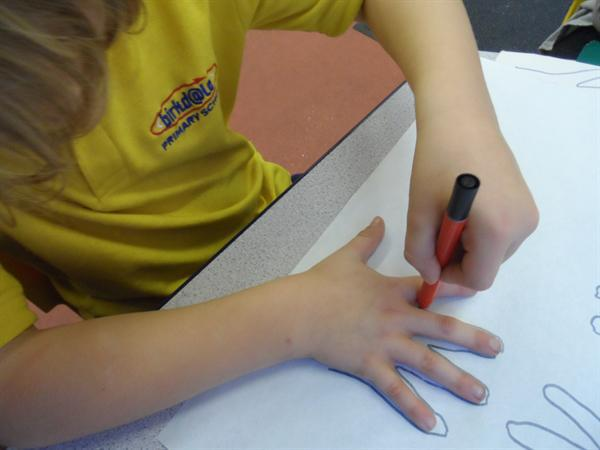 Drawing our hands to make a Christmas Tree