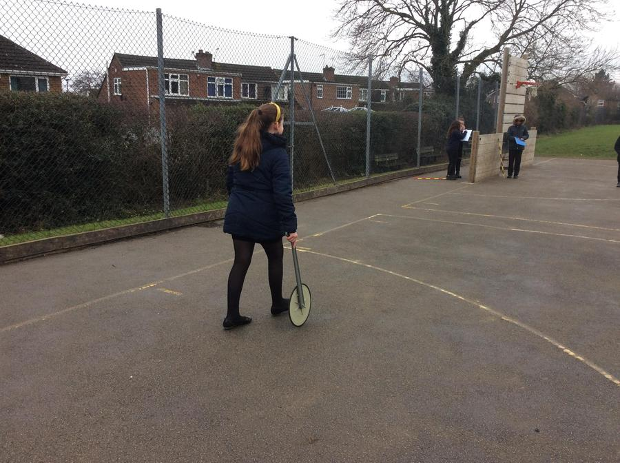 Using a trundle wheel to measure and work out the perimeter of the playground.