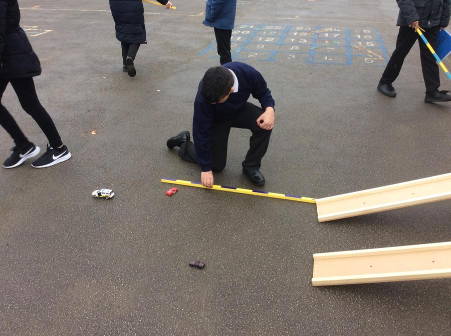 Measuring the distance of how far toy cars can travel.
