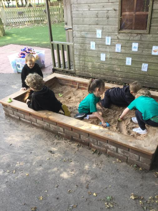 Enjoying making friends whilst playing in our sandpit!