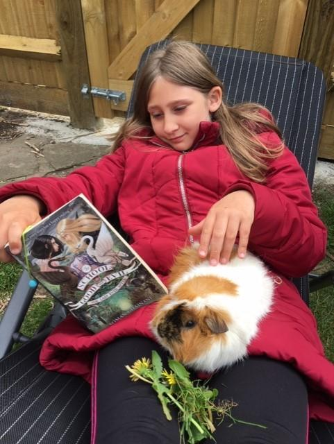 Charlotte reading with a rather adorable friend.