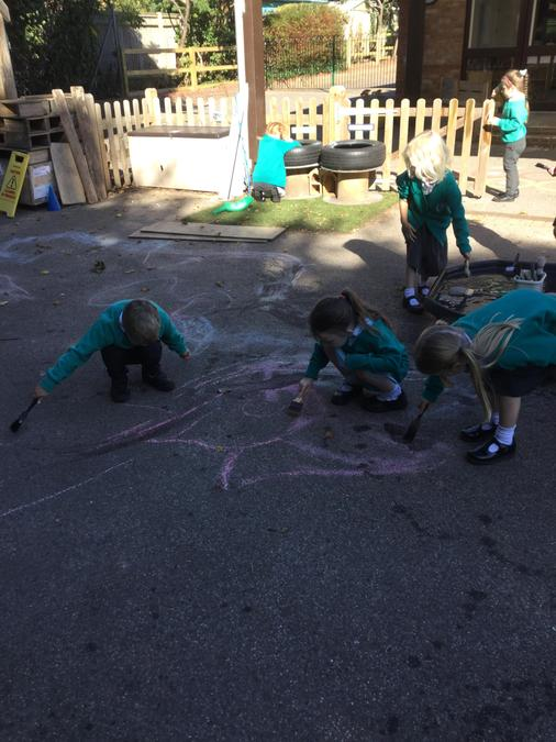 Developing our gross motor skills with the paint brushes and water