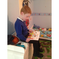 Harry (Year R) reading while mum ties his laces