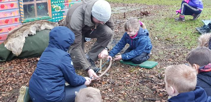 Children lighting a fire with a 'bow drill'.