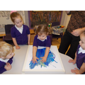 Using our hands to work the paint in to the canvas