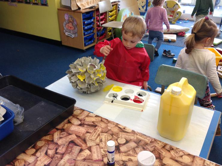 Seth helps to paint the bee hive
