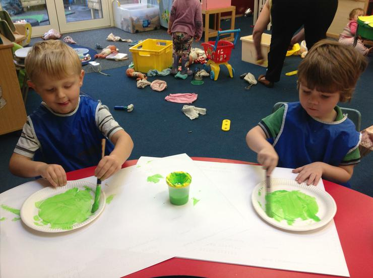 The children paint there plates green