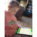 Practising her spellings using Scrabble.