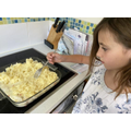 Rosie learning to make fish pie for dinner.