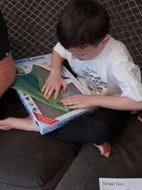Dylan making a paper aeroplane.