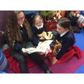 older pupils sharing stories with younger pupils and their bears