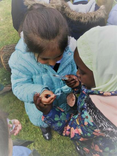 Ikra and Zaynab use a magnifying glass