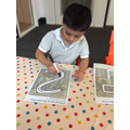 We use different mark making tools to develop our fine motor skills.