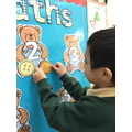 Counting buttons onto bears.