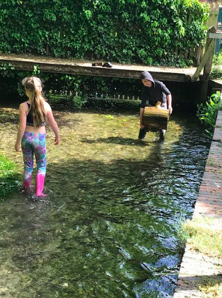 Michael exploring a stream with his sister.