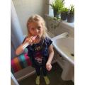 Holly timing brushing her teeth