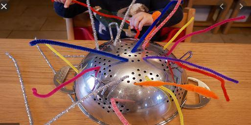 Threading pipe cleaners into a colander