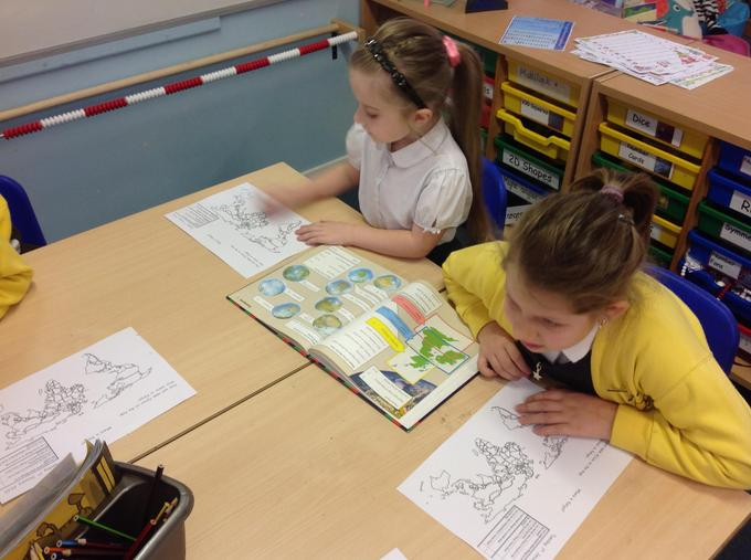 using an atlas to find Africa and Kenya