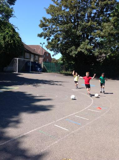 Dribbling carefully around the cones!