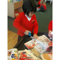 Using scissors to carefully cut out toys.
