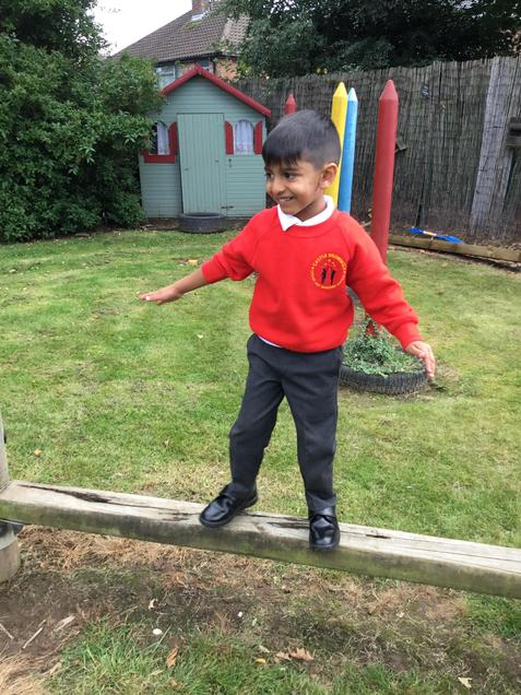 A child balancing on a beam.