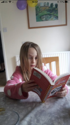 Niamh reading Diary of a Wimpy Kid