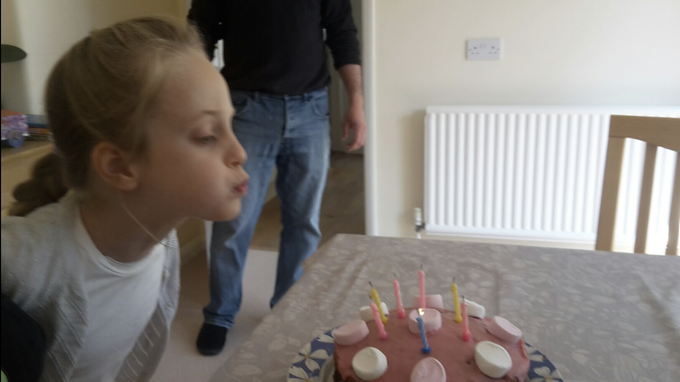 Niamh blowing out her birthday cake candles